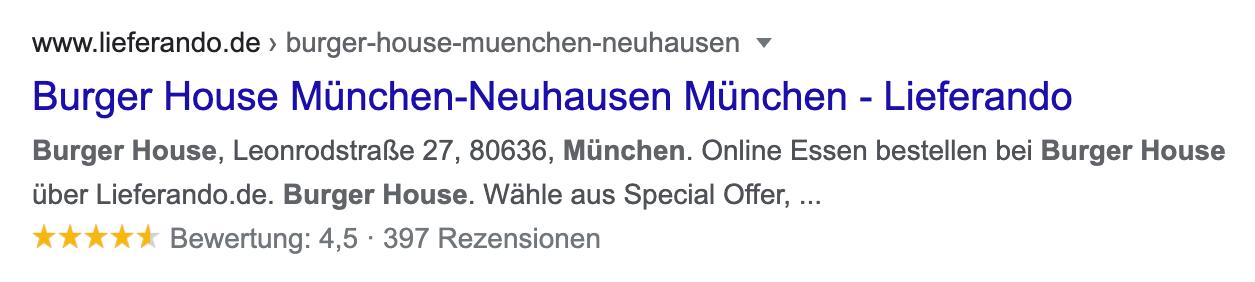 Beispielbild für ein Rich Snippet. Das Suchergebnis ist ein Burger House in München-Neuhausen auf der Seite lieferando.de. Das Ergebnis wird mit einem Rezensions-Snippet ausgeliefert. Unter der Meta-Description sind 5 Sterne zu sehen, von denen 4,5 gelb markiert sind.